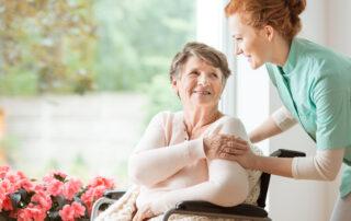 Young nurse helping an elderly woman in a wheelchair - Cardinal Hospice