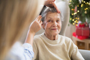 A health visitor combing hair of senior woman at home - Cardinal Hospice
